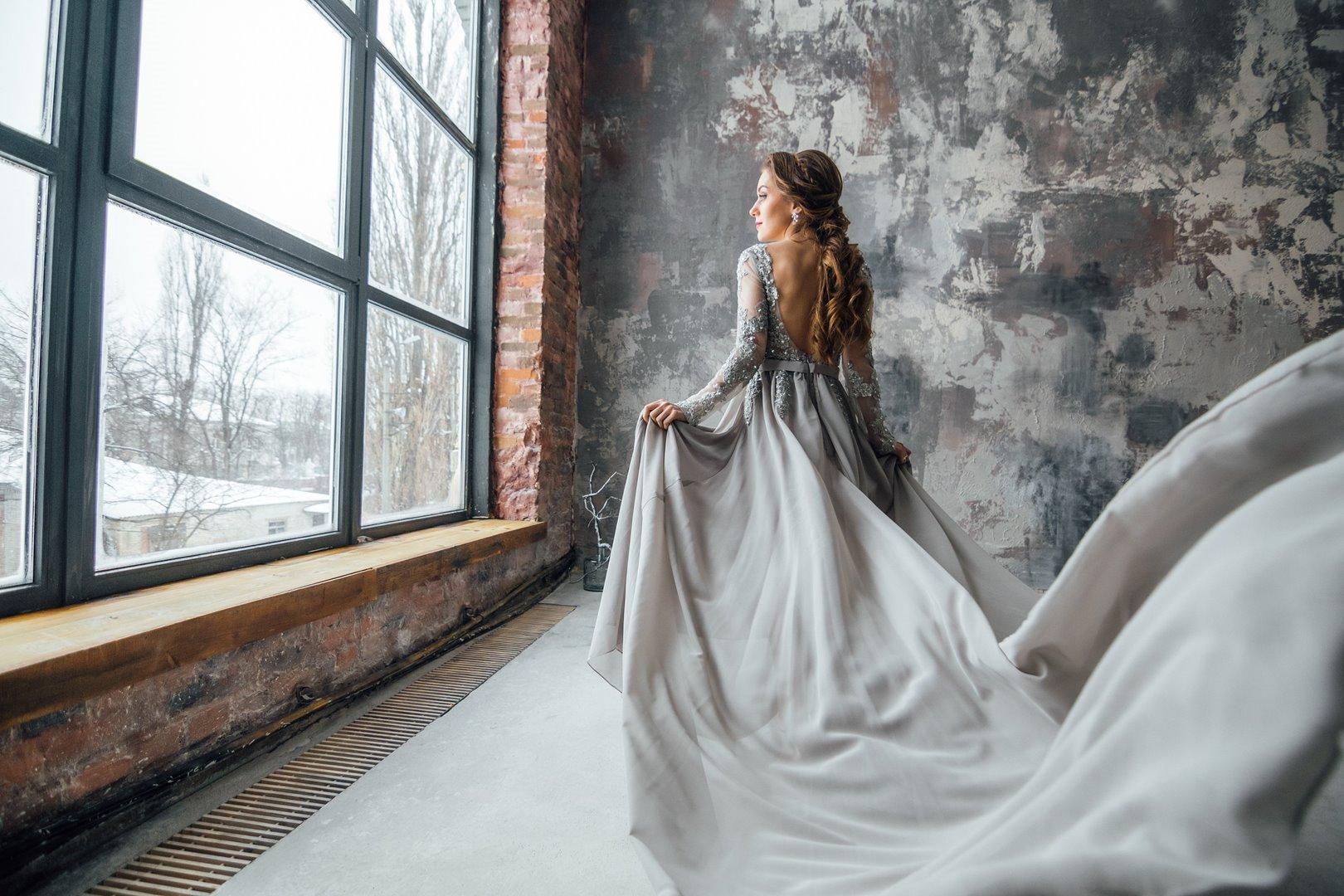 Femme en robe grise regardant par la fenêtre