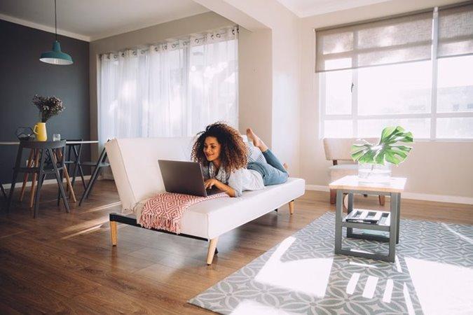 vrouw met laptop ligt op sofa