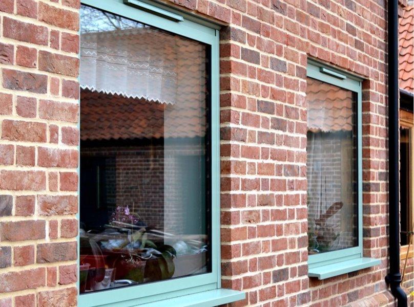 Chartwell green aluminium windows on a brick exterior