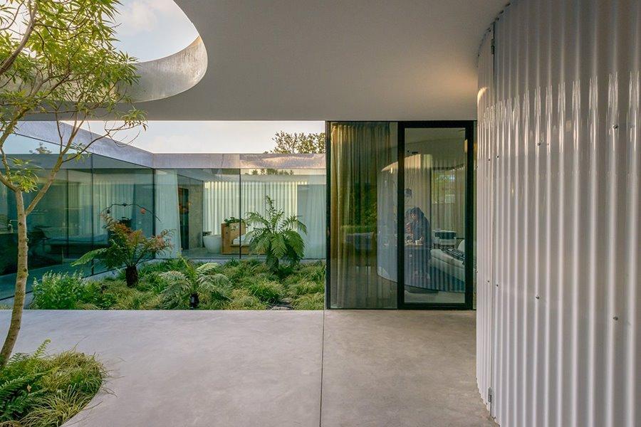 Afbeelding met gebouw, buitenruimte, grote ramen, planten en bomen