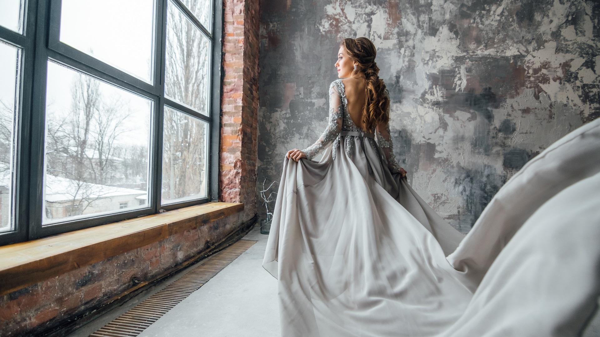Vrouw in grijze jurk achter aluminium kozijn zwart