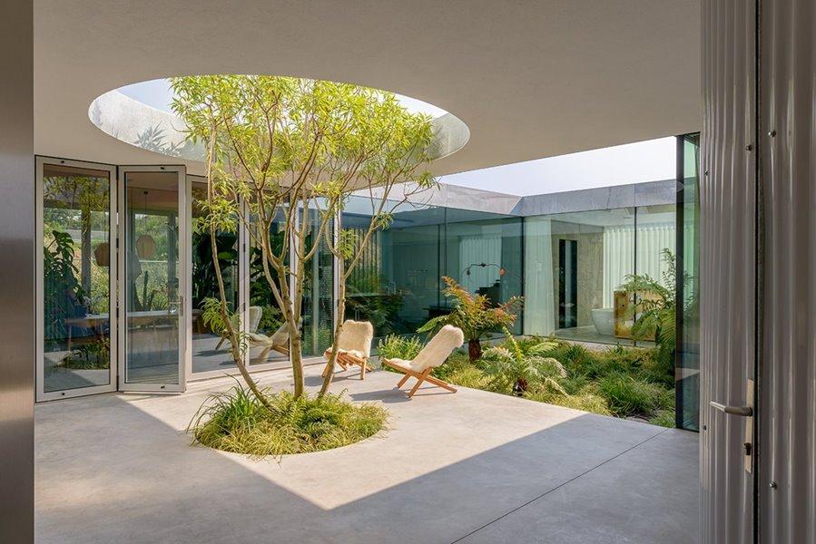 Afbeelding met gebouw, portiek, grote ramen en buitenleefruimte