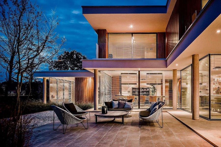 Moderne villa met grote aluminium schuiframen en zicht op terras