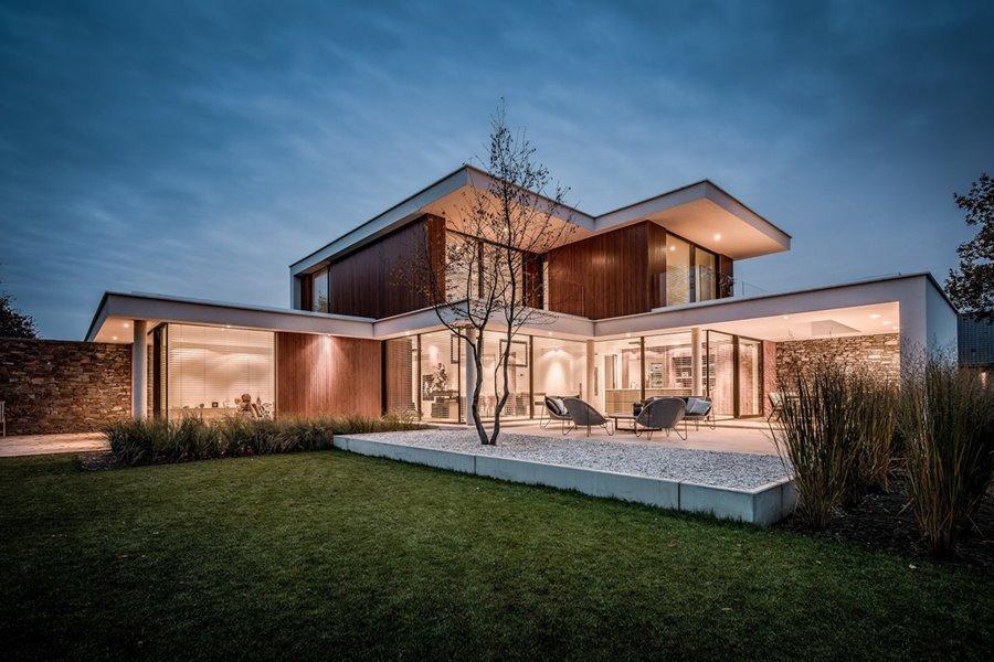 Moderne villa grote aluminium schuiframen en zicht op de groene tuin