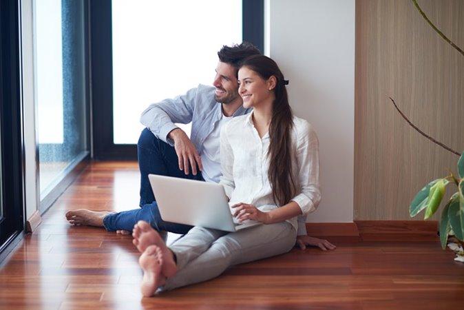 Man en vrouw zittend op vloer met geopende laptop