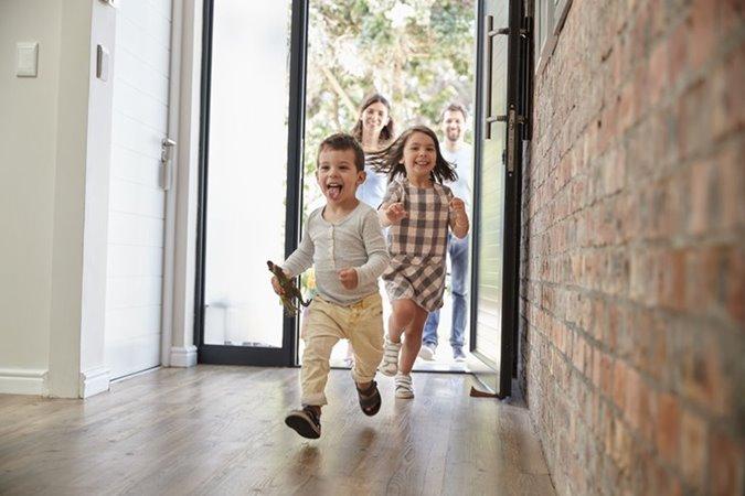 Kinderen rennen door openstaande deur huis binnen