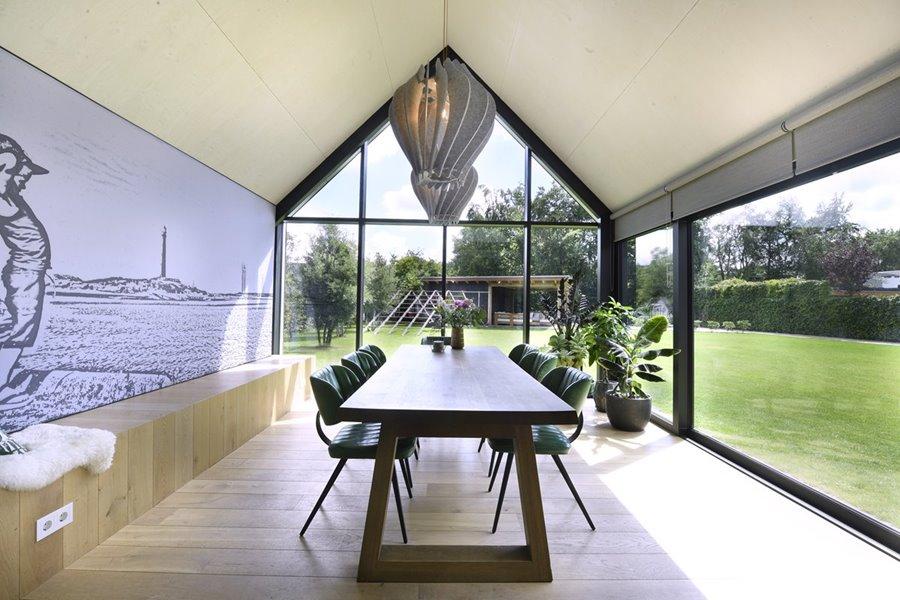 eetkamer met grote aluminium ramen met zicht op tuin