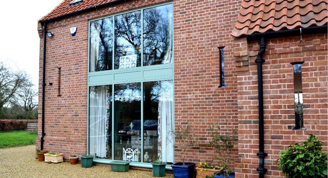 House with chartwell green finish aluminium windows