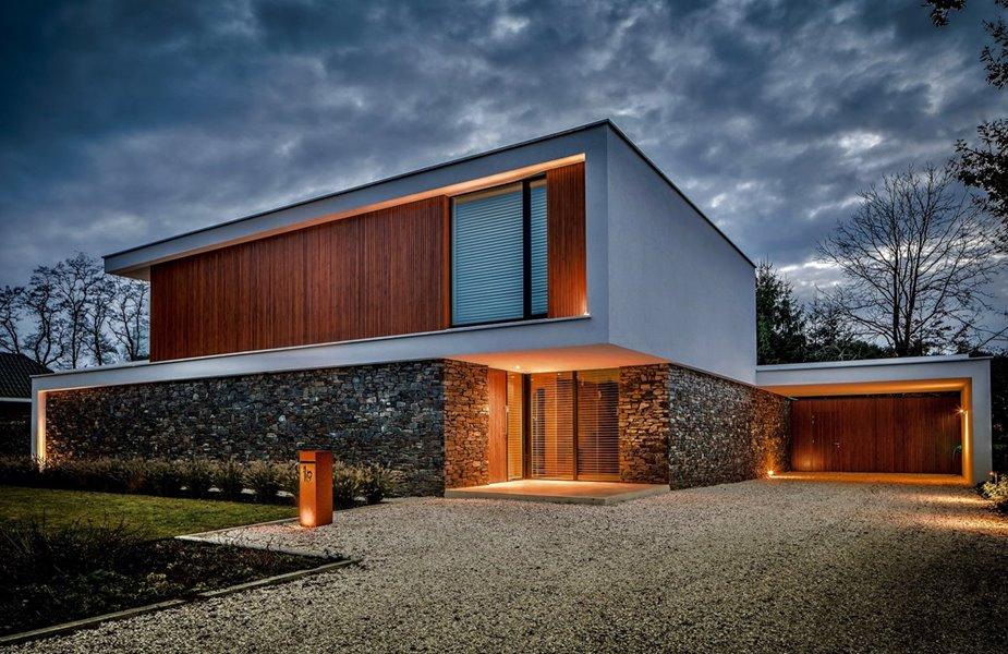 Moderne villa met moderne voorgevel met natuursteen en hout