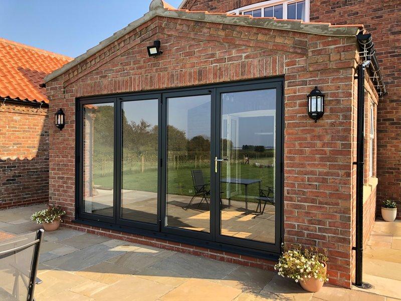 Aluminium black bifold doors on an extension