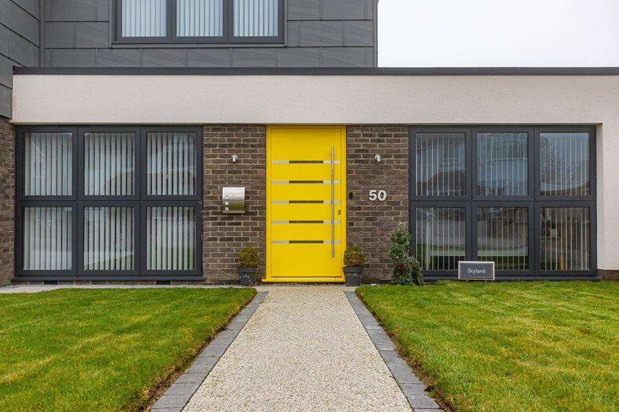 Aluminium yellow entrance door on a lovely house
